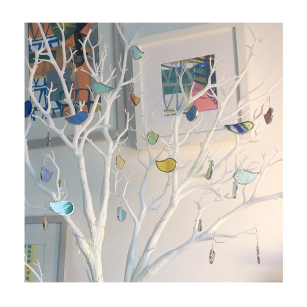 mini glass birds decorating a twig tree